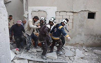 """Defesa Civil da Síria (também conhecido como """"Capacetes Brancos"""") resgatam uma pessoa ferida após o bombardeio na cidade de Khan Sheikhun na zona rural da província rebelde de Idlib."""