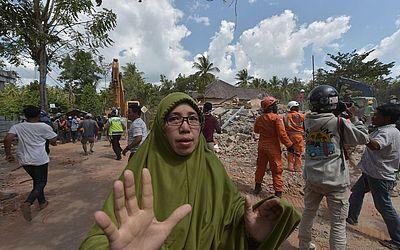 Equipes de busca e salvamento da indonésia logo após um tremor atingir novamente a área de Tanjung na ilha de Lombok.