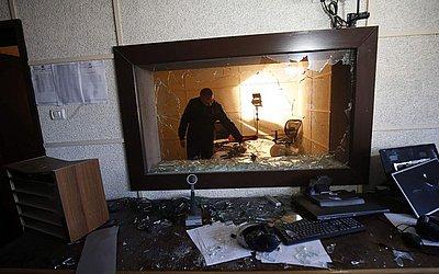 Um funcionário da emissora de rádio e tv  estatal da palestina inspeciona os danos em um dos estúdios, depois que homens armados supostamente invadiram o prédio na cidade de Gaza.