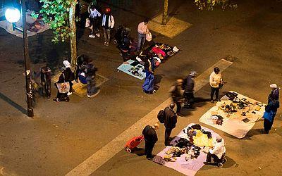 Camelôs vendem objetos de segunda mão, tais como roupas, sapatos, celulares, carregadores do telefone e DVDs em um mercado ilegal, mas semi permanente em La Chapelle, Paris.