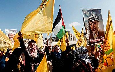 Apoiadores do exilado político palestino e ex chefe de segurança do movimento Fatah, Mohammed Dahlan, levam cartazes de Yasser Arafat, durante uma cerimônia que relembra os 14 anos de morte do líder palestino.