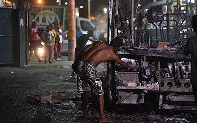 Homem retira sucata de ônibus após incêndio