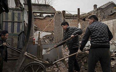 Trabalhadores carregam os restos de uma casa destruída em um carrinho de mão durante esforços de reconstrução, no bairro de Hutong, em Pequim.