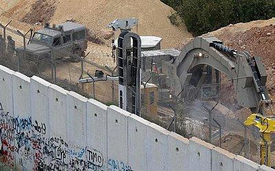 Máquinas trabalham do lado de fora da fronteira da aldeia libanesa de Kfar Kila . O exército de Israel disse que tem descoberto túneis de Hezbollah infiltrando seu território a partir do Líbano e iniciou uma operação para destruí-los.