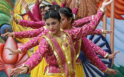 Indianas dançam em frente à escola pública de Amritsar.