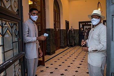 Funcionários aferem a temperatura dos que entram no hotel