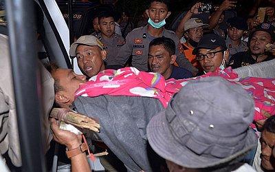 Voluntários resgatam um sobrevivente do desabamento da mina ilegal na vila Beck, subdistrito de Lolayan em Bolaang Mongondow, em Celebes do Norte, na Indonésia. Dezenas de pessoas ficaram soterradas e pelo menos quatro pessoas morreram.