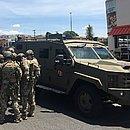Policiais armados próximos a um carro do FBI estão no local