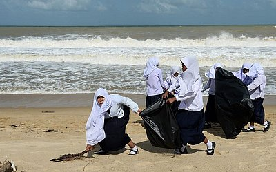 Estudantes se juntam aos soldados tailandeses para limpar os destroços deixados pela tempestade tropical Pabuk na praia de Narathiwat Ban Thon. Foram ventos de até 75 quilômetros (45 milhas), trazendo chuvas pesadas.