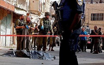 Membros das forças de segurança israelenses cercam o corpo de um palestino na cidade de Hebron, na Cisjordânia ocupada. Um homem palestino atacou um soldado israelense perto de um local sagrado antes de ser morto a tiros.