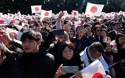 Japoneses acenam para o ano novo durante a cerimônia oficial quando o Imperador Akihito e membros de famílias reais expressam seus votos de bem-aventurança.