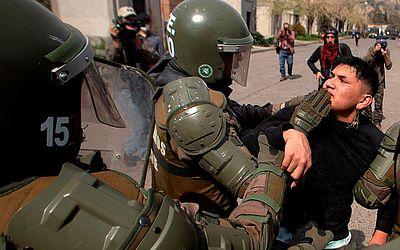 """A polícia chilena detém um ativista da Organização de Direitos Humanos Chilena """" Pessoas detidas e Desaparecidas"""" durante as comemorações dos 45 anos do golpe military que depôs Salvador Allende, em Santiago."""