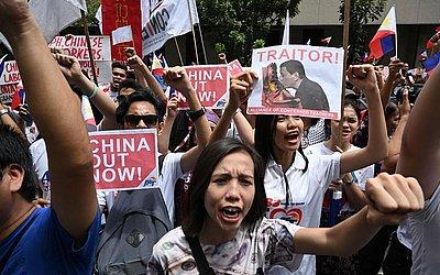 Manifestantes anti-China protestam em frente ao escritório consular da China, no distrito financeiro de Manila. Eles se opõe a influência crescente da superpotência asiática nas Filipinas.