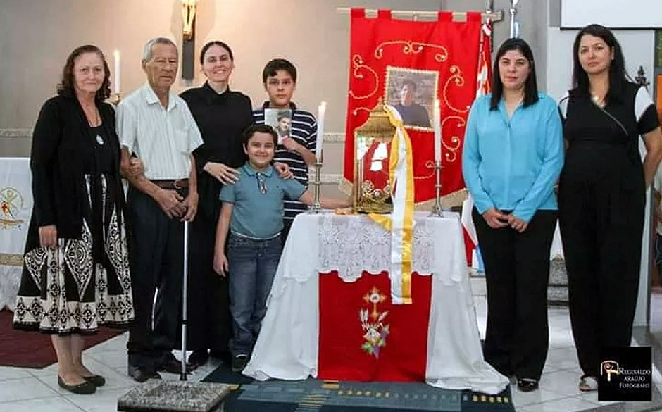 Menino que recebeu milagre e patentes em paróquia no Mato Grosso do Sul, com foto de Acutis ao fundo