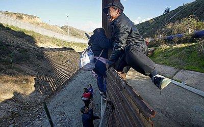 Migrantes hondurenhos escalam a cerca da fronteira EUA-México em Tijuana, no México.