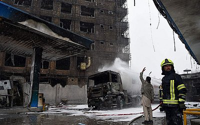 Bombeiros afegãos trabalham na área em que um prédio pegou fogo ontem à noite em um posto de gasolina em Charahi Abdul Haq em Cabul. Três pessoas foram encontradas mortas e 19 feridos.