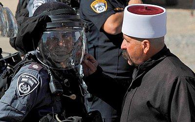 Um druso argumenta com um policial israelense em frente a um centro de pesquisa na aldeia de Majdal Shams em Golã, durante um protesto da Comunidade contra eleições municipais.