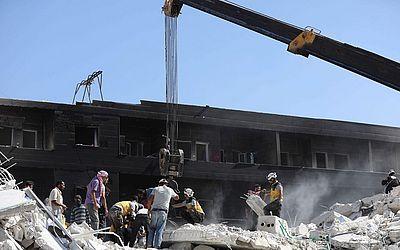 Trabalhadores de resgate buscam sobreviventes entre os escombros dos edifícios destruídos após a explosão num depósito de armas em uma área residencial no norte de Idlib , na cidade de Sarmada, na Síria.
