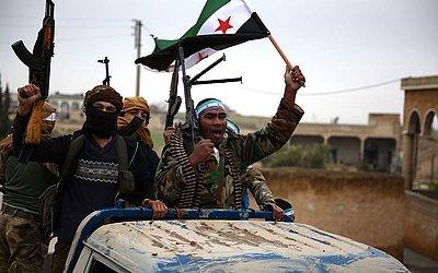 Combatentes turcos aliados aos rebeldes sírios levantam a bandeira de oposição ao chegarem à  cidade de Qirata,  depois de deixar seus quartéis em Jarabulus, à caminho para Manbij.