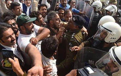 Partidários do líder da oposição detido por corrupção, Shahbaz Sharif, enfrentam a polícia na entrada do Tribunal em Lahore.