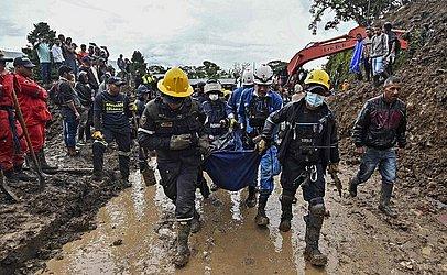Trabalhadores resgatam vítimas de um deslizamento de terra em Rosas, no departamento de Valle del Cauca, no sudoeste da Colômbia, onde pelo menos 14 pessoas morreram e outras cinco ficaram feridas com o soterramento de 08 casas.