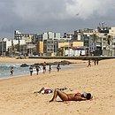 Mulher toma sol no primeiro dia de reabertura das praias