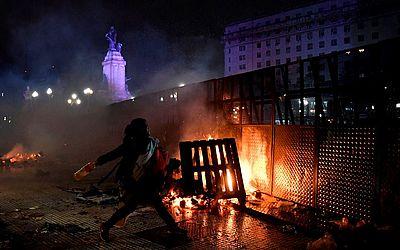 Uma mulher lança um coquetel molotov no Congresso Nacional em Buenos Aires, após os senadores rejeitaram o projeto de lei para legalizar o aborto.