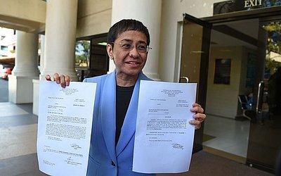 Maria Ressa, CEO e editora executiva do portal online Rappler mostra o mandado da ordem de prisão após pagamento de fiança em um tribunal em Manila. O site de notícias fez oposição ao Presidente Duterte e foi acusado de fraude fiscal.