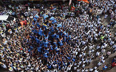 Devotos hindus formam uma pirâmide humana em uma tentativa de alcançar e quebrar um dahi-handi (pote de barro) suspenso no ar durante as celebrações do Janmashtami, que marca o nascimento de Krishna, em Mumbai.