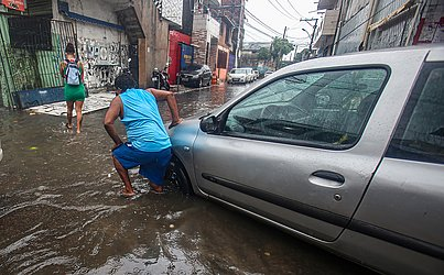 Carros ficaram presos em bueiros e buracos na pista escondidos pela água.