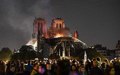 Pariesisenses e turistas observam os trabalhos dios bombeiros na Catedral de Notre-Dame. A cathedral é o monumento histórico mais visitado da Europa.