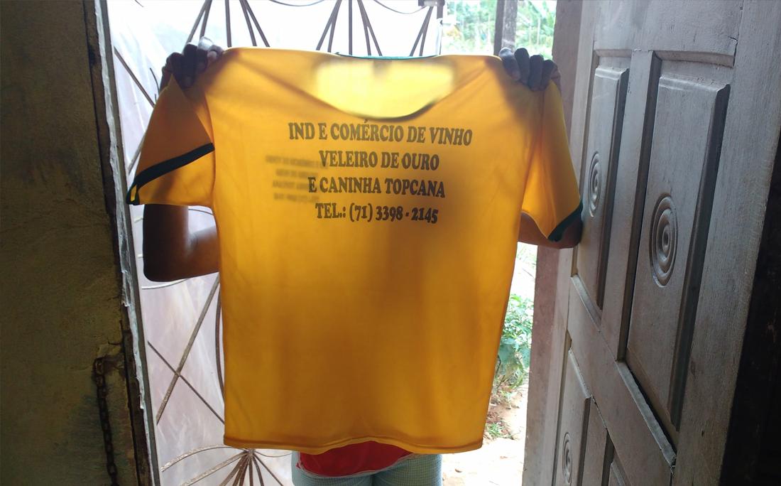 Funcionária mostra camiseta que indicam produtos fabricados no local