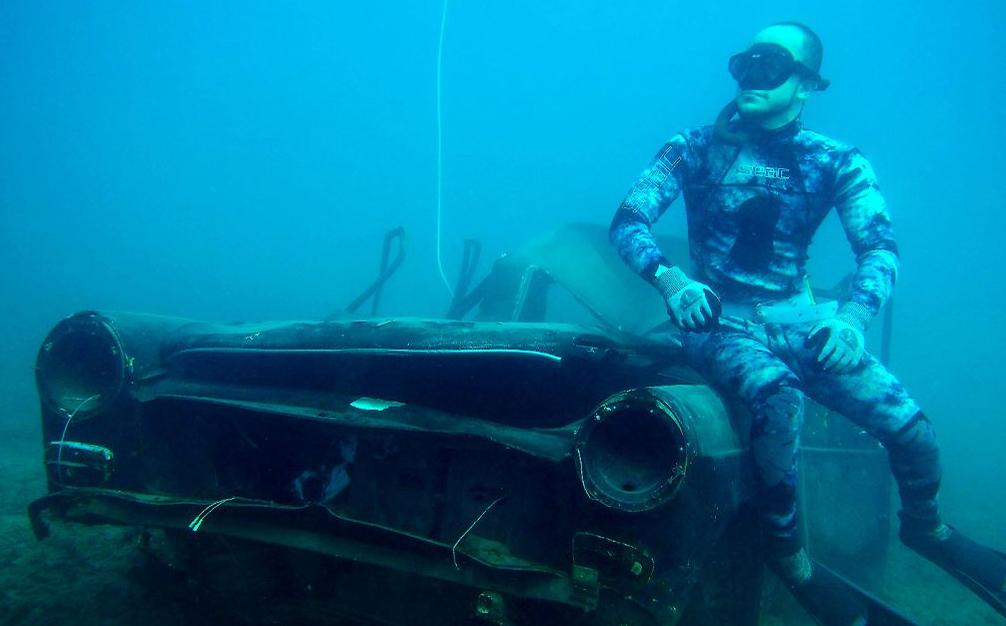 Um mergulhador posa ao lado de um automóvel submerso na costa do Porto libanês de Sidon,
