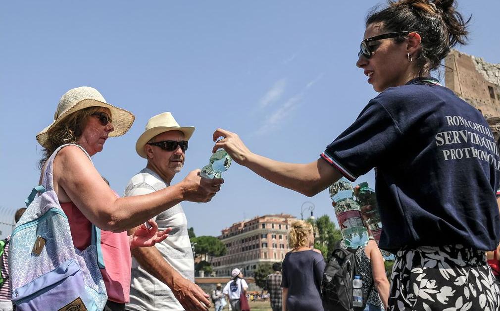 Membros da Proteção Civil italiana (Protezione Civile) distribuem garrafas de água em frente ao Coliseu antigo, no centro de Roma, pois a Itália também enfrenta uma onda de calor, com temperaturas próximas a 40 graus Celsius.
