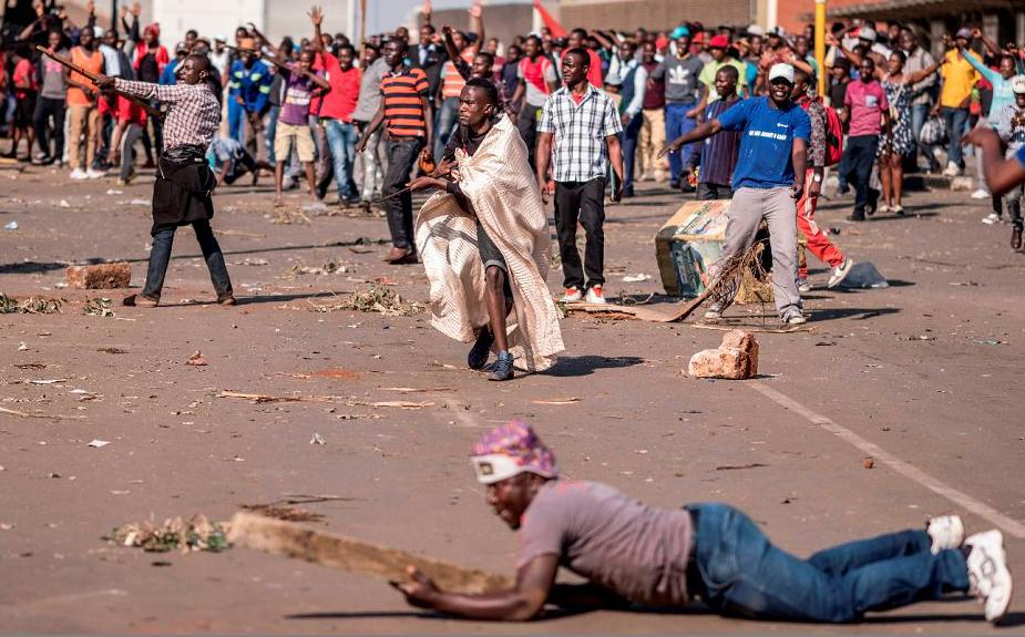 Eleitores do partido MDC do Zimbabue protestam contra suposta fraude nas eleições na frente da sede do partido em Harare.