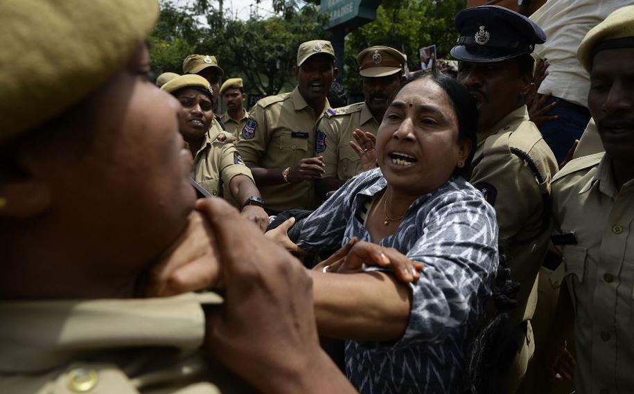Ativista dos direitos das mulheres briga com a polícia durante um protesto contra a prisão do poeta indiano e militante Varavara Rao em Hyderabad.