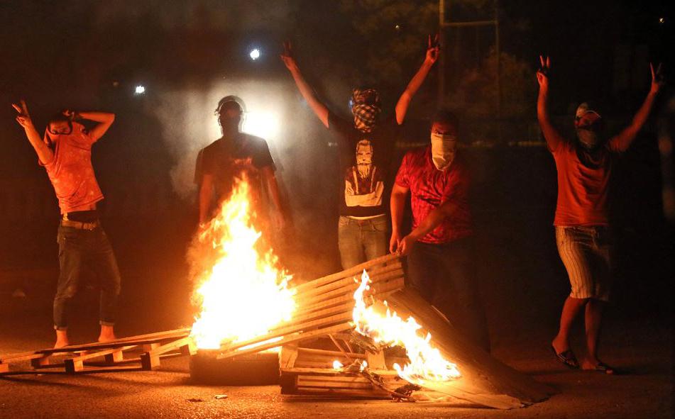 Manifestantes iraquianos protestam queimando peças de madeira contra a falta de serviços básicos, como energia, desemprego, má gestão do estado e a falta de água limpa.
