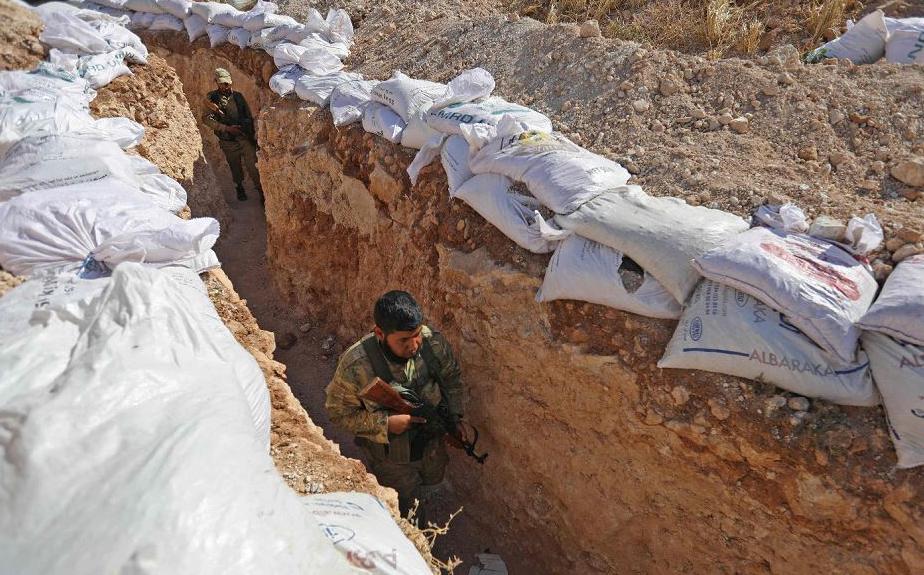 """Rebelde sírio à frente da recém formada """"frente de libertação nacional"""" percorre uma trincheira na zona rural da província de Idlib."""
