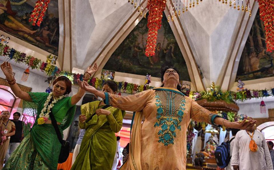 Dança de devotos hindus durante o festival de Krishna Janmashtami no templo ISKCON Deli em Nova Deli.