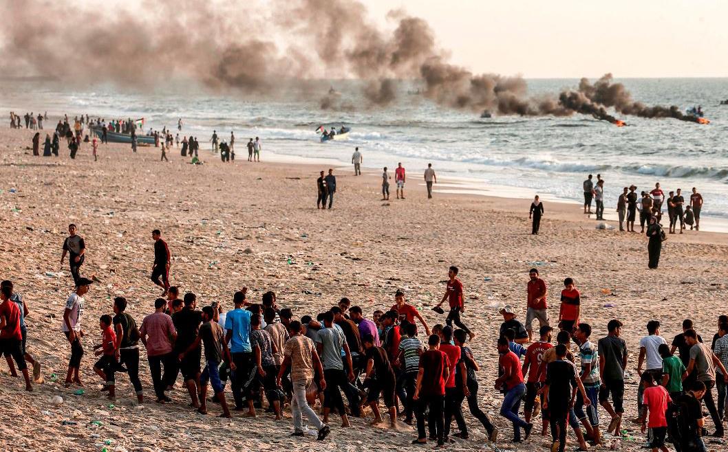 Manifestantes palestinos carregam um homem que foi ferido durante confrontos com as forças israelenses em uma praia ao longo da barreira do mar de Gaza na fronteira com Israel perto de kibutz Zikim, ao norte de Beit Lahia.