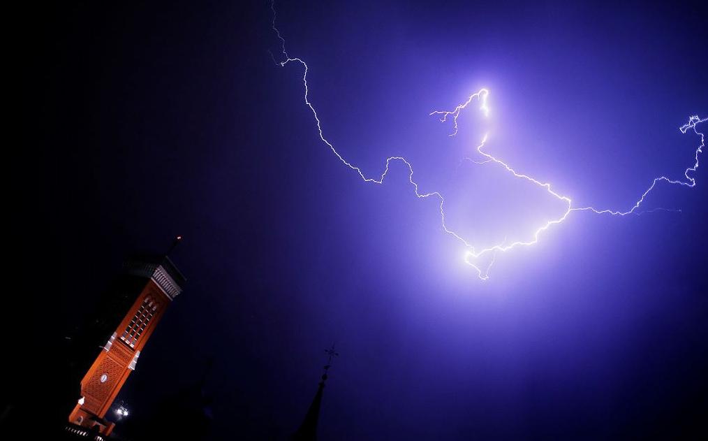 Um relâmpago ilumina o céu sobre a torre da Igreja Santa Cruz em Madrid.
