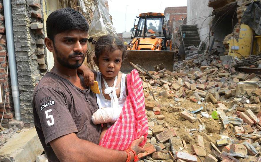 Raj Kumar carrega sua filha ferida Rakhita um dia após a explosão em uma fábrica de biscoito ilegal em Amritsar. Seis pessoas ficaram feridas e os telhados de três casas, incluindo a fábrica foram destruídos após a explosão.