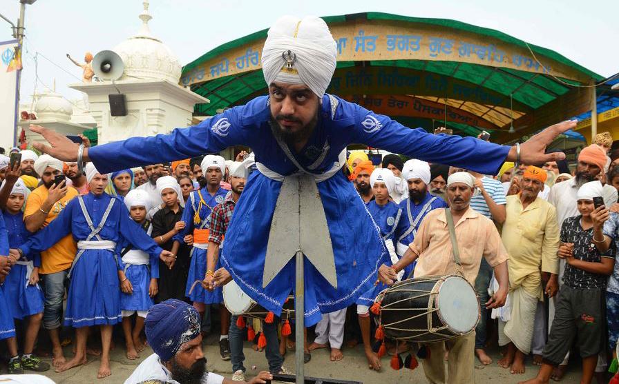 Um indiano Sikh executa a 'Gatka', uma arte marcial, durante a procissão religiosa do Gurudwara Ramsar, no Templo Dourado em Amritsar.