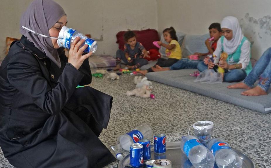 Família síria faz mascaras improvisadas como forma de se precaver contra futuros ataques à cidade de Idlib.
