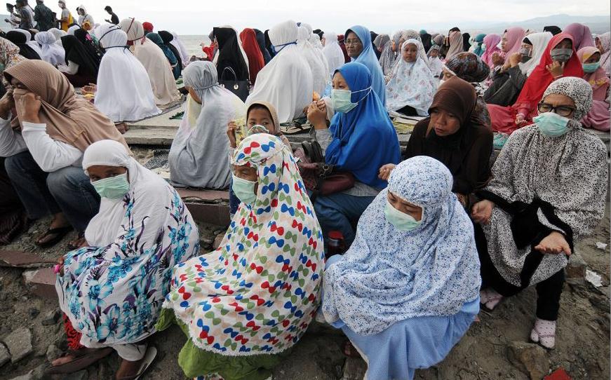 Os muçulmanos indonésios reúnem-se para uma oração em massa na vila de Talise em Palu após o terremoto e tsunami que atingiu a área.