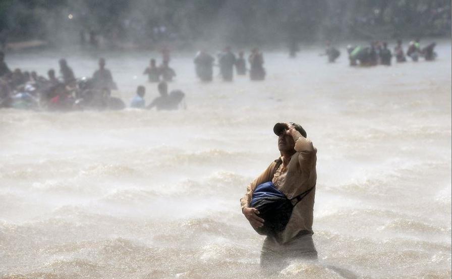 Migrantes atravessam o rio Suchiate de Tecun Uman na Guatemala para Ciudad Hidalgo, no México, depois que uma cerca de segurança na ponte internacional foi reforçada para impedir a passagem da caravana.