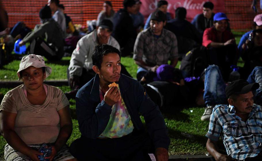 """Migrantes salvadorenhos esperam na Praça """"Salvador del Mundo"""", em San Salvador para se juntar à caravana de milhares de centro-americanos que rumam para os EUA."""