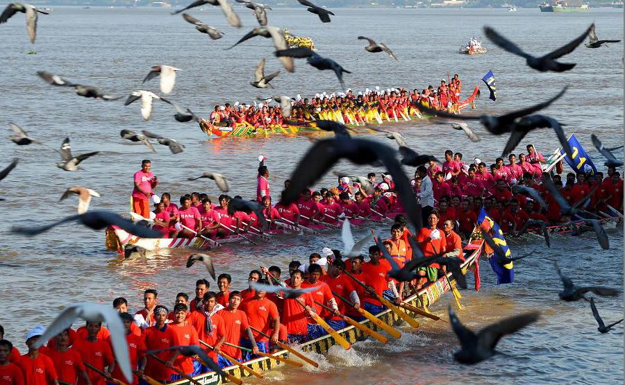 Cambojanos remam seus barcos de dragão durante a competição do Festival da Água em Phnom Penh.