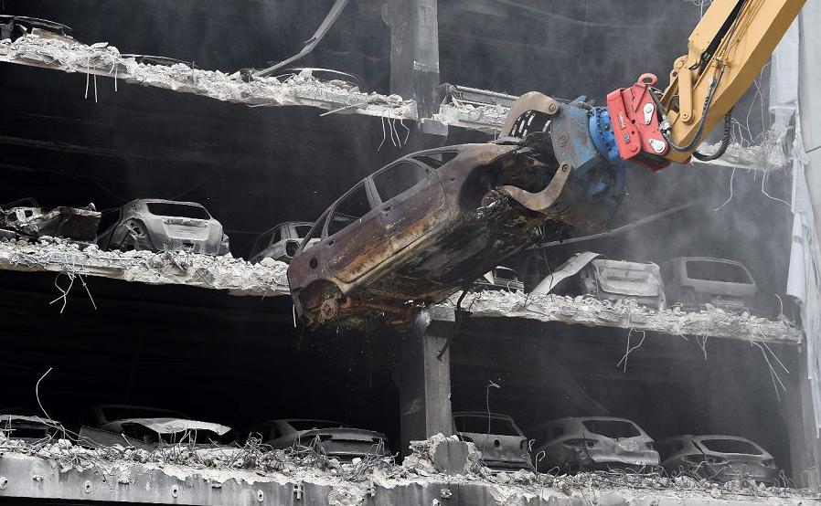 Carro incendiado é removido do estacionamento afetado pelo fogo perto da Arena de Liverpool, norte da Inglaterra. Um incêndio em 2017 destruiu o multi-estacionamento e aproximadamente 1.400 veículos queimaram à beira-mar.