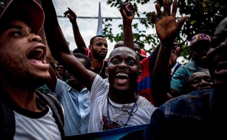 Partidários do candidato presidencial de República Democrática do Congo Martin Fayulu cantam e dançam durante sua chegada em Kinshasa para lançar sua campanha.